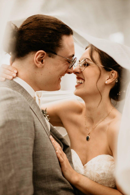 Glückliches Paar bei der Hochzeit unter dem Schleier in Köln